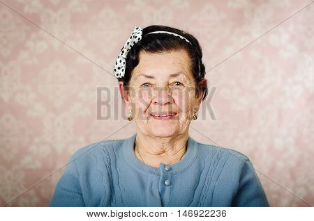 Older cute hispanic woman wearing blue sweater and polka dot bowtie on head smiling happily in front of pink wallpaper.
