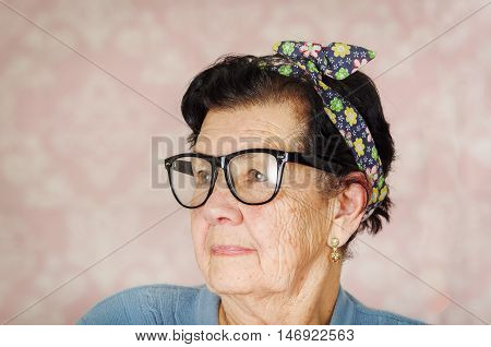 Older hispanic cute woman with flower pattern bow on her head wearing blue sweater and black large framed glasses looking to the side of camera.