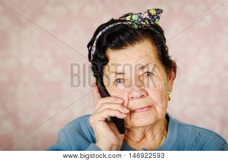 Older hispanic cute woman with flower pattern bow on her head wearing blue sweater in front of pink wallpaper talking into black cellphone.