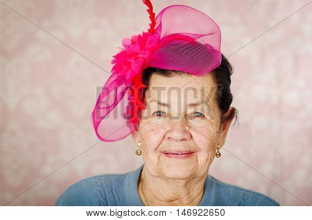 Older cute hispanic woman wearing blue sweater, large pink ribbon on head loking into camera..