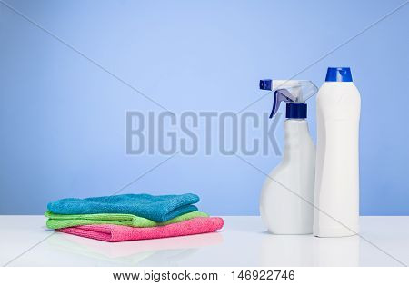 Cleaning concept backround. Assorted products isolated on white and blue backdrop. Studio product shot for advertising, website or blog.