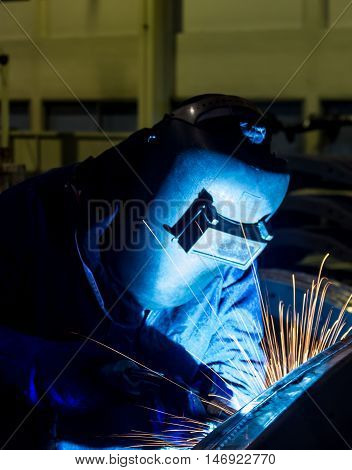 welder welding Industrial automotive part in factory