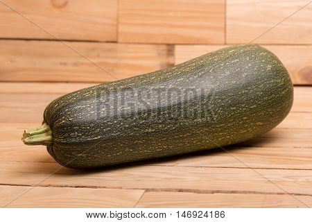 One green zucchini vegetable shown whole on a yellow wooden background.