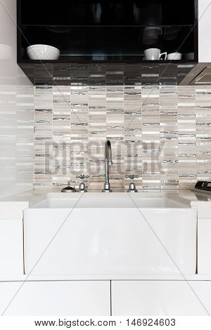 Close up of a deep white kitchen sink and feature tiled splashback