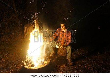 Handsome male model sitting at fire pit.