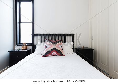 Modern light bright bedroom with wooden shaker bed and white linen