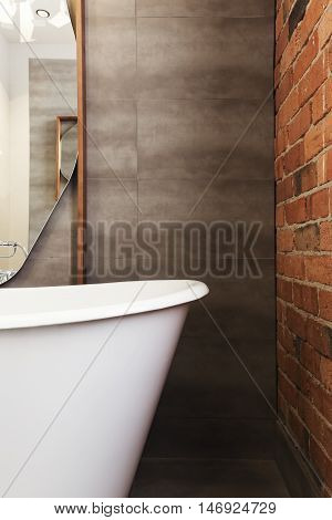 Close up of bath end against grey tiled wall background with text space