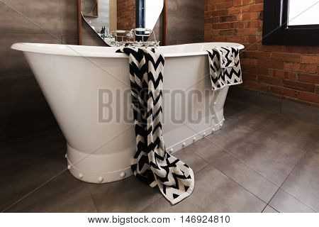 Styled bath towel draped over a freestanding vintage style bath tub