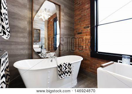 Horizontal version freestanding vintage style white bath tub in renovated warehouse apartment