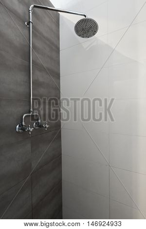 Close up of rain shower vintage tap in grey and white bathroom