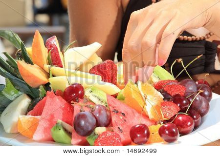 Young smiling woman with fruits salad