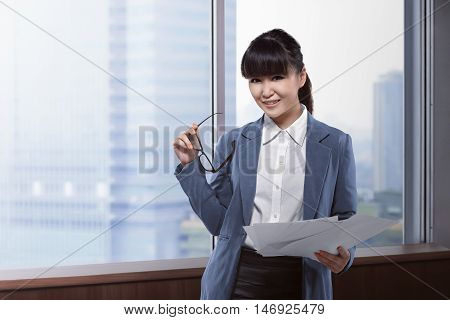 Asian Business Woman Holding Paper And Glasses