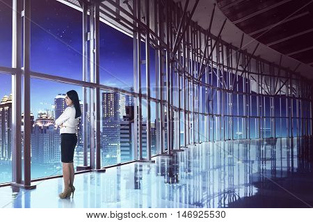 Asian business woman looking the city at night. Leadership concept image