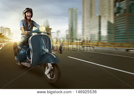 Asian Woman Riding Scooter And Wearing Helmet