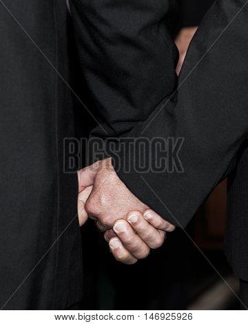 Two men holding hands wearing dark suits.