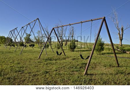 Three old swingers in a rural country school playground