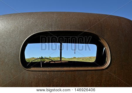 The rear cab view an old rusty pickup from back window space through the front split windshield space