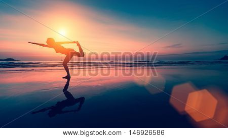 Female silhouette performs yoga exercises on the beach at sunset.