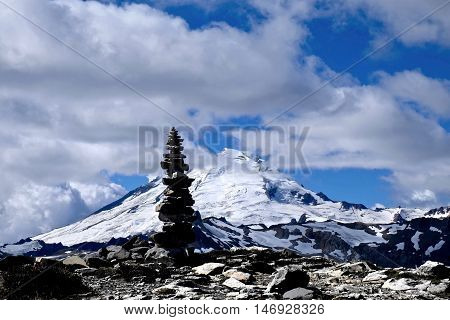 Stone cairn silhouette against snow capped Mount Baker. Cascade Mountains. Mount Baker National Forest. Seattle. Washington. USA.