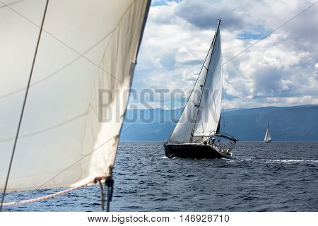 Sailing ship luxury yacht with white sails during a race regatta in the Sea.