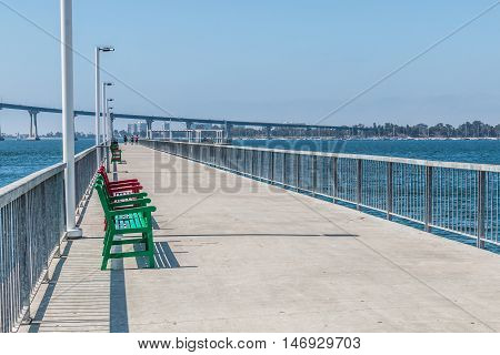 Pier with benches at Cesar Chavez Park in San Diego, California with Coronado Bridge.