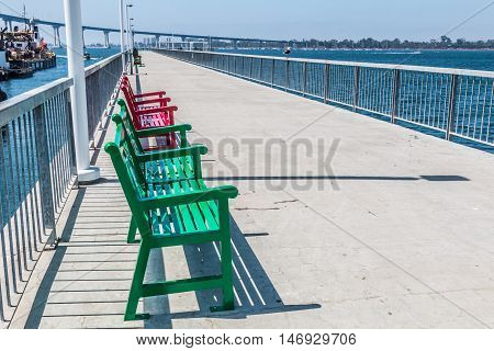 Benches on pier at Cesar Chavez Park in San Diego, California, with Coronado Bridge and San Diego bay in the background.