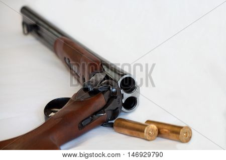 Opened double-barrelled gun with two bullets close-up photo isolated on white background