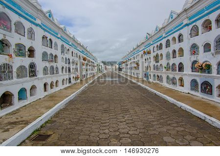 TULCAN, ECUADOR - JULY 3, 2016: central path of the cementery, graves located on the both sides of the path.