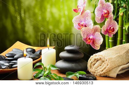 Spa and wellness setting with zen stone candles towels and flower.