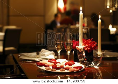 Romantic table setting with Chocolates, Candle and Wine