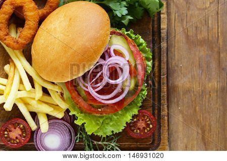 homemade hamburger with vegetables and a green salad