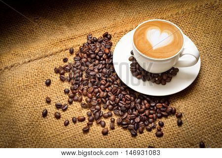 A cup of coffee with latte art of heart and coffee bean on texture background