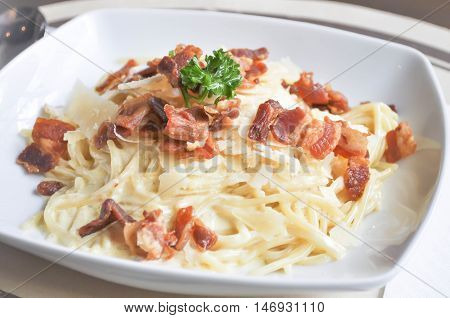 Spaghetti carbonara dish. Pasta with bacon in a white dish.