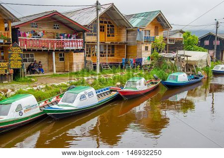 PASTO, COLOMBIA - JULY 3, 2016: some colorfull boats parked on the river next to some shops.