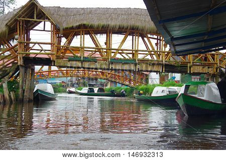 PASTO, COLOMBIA - JULY 3, 2016: some small boats parked on the river under some small wood bridges on la cocha lake.
