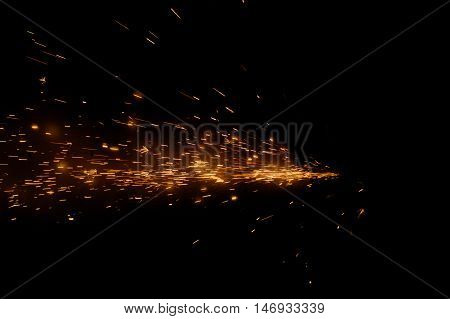 Fire sparks on a black background during metal cutting