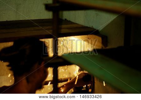 Metal worker cutting metal with fire sparks