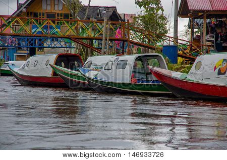 PASTO, COLOMBIA - JULY 3, 2016: some boats parked on the shore with a bridge and some houses as background.