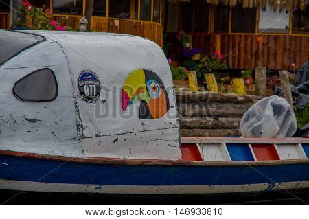PASTO, COLOMBIA - JULY 3, 2016: colorfull toucan painted in one boat parked in a shore of la cocha lake.