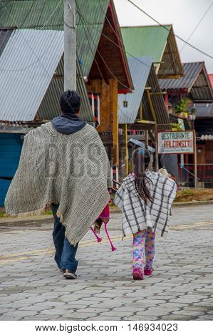 PASTO, COLOMBIA - JULY 3, 2016: man walking with a little girl dressed with traditional clothes in a small location in la cocha lake.