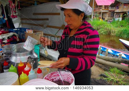 PASTO, COLOMBIA - JULY 3, 2016: unidentified woman preparing a dessert with wafer and caramel.