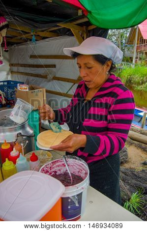 PASTO, COLOMBIA - JULY 3, 2016: unidentified woman preparing a dessert with caramel and a wafer in a location close to la cocha lake.