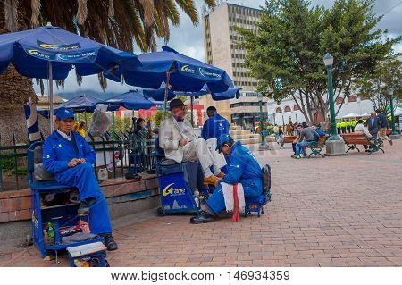 PASTO, COLOMBIA - JULY 3, 2016: unidentified man cleaning the shoes of an old man with white suit.