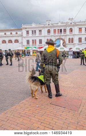 PASTO, COLOMBIA - JULY 3, 2016: policeman standing next to a trained police dog in the central square.