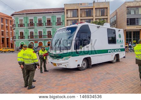 PASTO, COLOMBIA - JULY 3, 2016: unidentified police officers standing next to a police bus parked on the square.