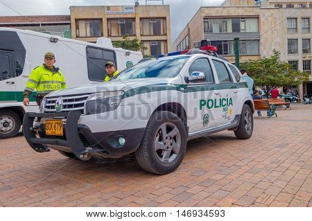 PASTO, COLOMBIA - JULY 3, 2016: unidentified police officers standing next to a police car parked on the central square of the city.