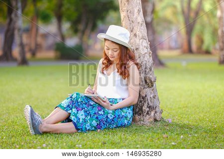 Beautiful asian woman sitting with pen writing on notebook on grass outside