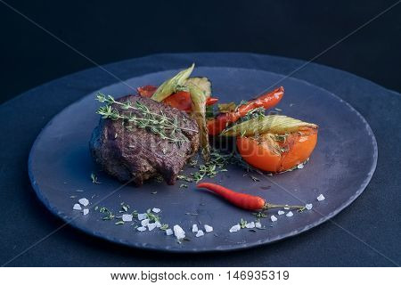 Grilled beef steak with baked vegetables on plate