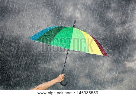 Hand Holding Multicolored Umbrella Under Dark Sky With Rain