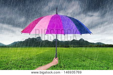 Hand Holding Multicolored Umbrella With Falling Rain At Khao Jeen Lae, Mountain At Lopburi, Thailand
